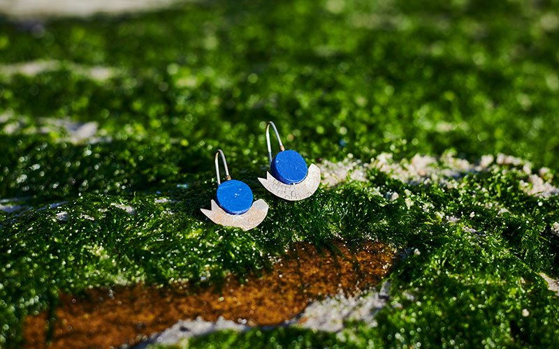 Blue and silver earrings on a green mossy rock.