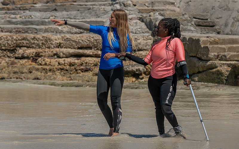 Two women stand on the beach, one with a crutch and the other pointing to something in the distance.