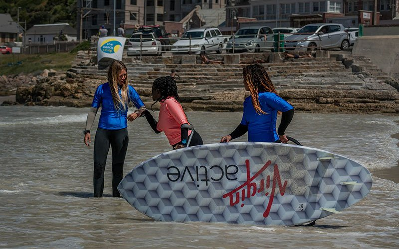 Three women with a surfboard standing in shallow waters on a beach.