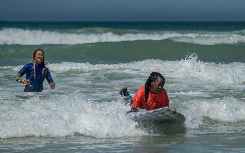 Woman in orange rash vest catches a small wave.