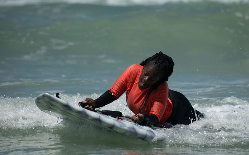 Woman lying on a surfboard catching a wave.