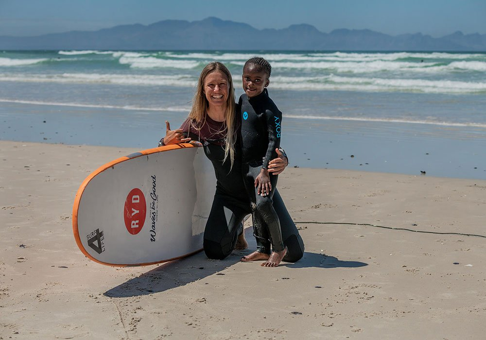 A smiling woman and a young child kneel on a beach in wetsuits with a surfboard.