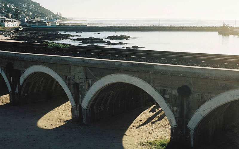 Railway track with tidal pools and ocean in the background.