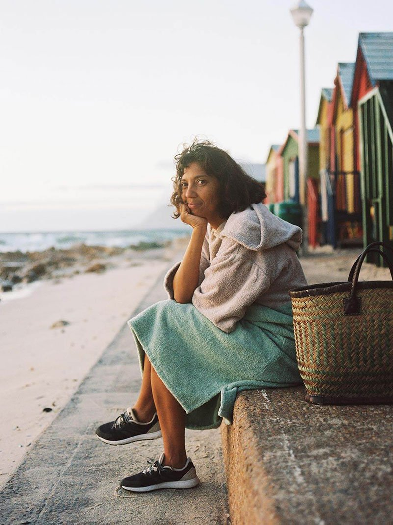 Woman in a towel sitting on the steps at Muizenberg beach.