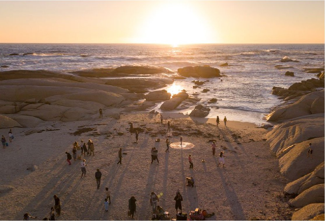 People walking along the beach at sunset.